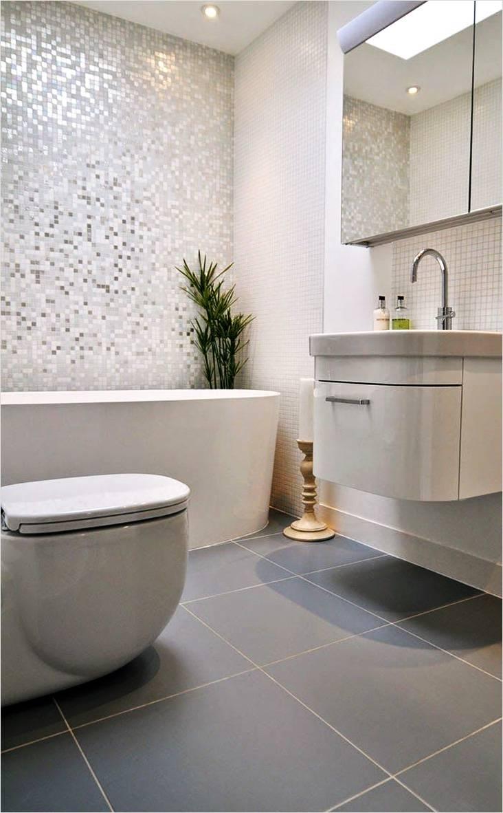 Интерьер маленькой ванной в светлых тоннах со стенами выложенными мозаикой