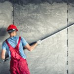 industrial worker with plastering tools renovating a house. buil